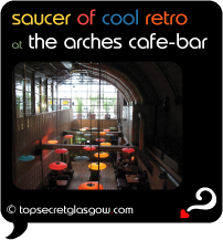 Top Secret Quote Bubble in black, with photo of Arches Cafe Bar Interior, glowing multi-coloured saucer lights suspended low from high railway arch space.  Caption: 'saucer of cool retro'