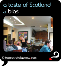 Top Secret Quote Bubble in black, with photo of light bright interior of Blas;  blonde waitress in black serving drinks to group of guests. Caption: 'a taste of Scotland'