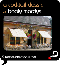 Top Secret Quote Bubble in black, with photo of exterior of Booly Mardys; blond sandstone with cream awnings and bright hanging floral baskets.  Pavement tables and chairs. Caption: 'a cocktail classic'