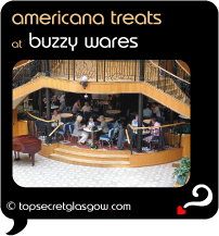 Top Secret Quote Bubble in black, with photo of exterior of Buzzy Wares; raised patio tucked under the grand wooden and wrought-iron stairway of Princes Square.  Diners at tables and chairs.  Grand piano to left side.  Caption: 'americana treats'