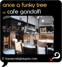Top Secret Quote Bubble in black, with photo of  Cafe Gandolfi, interior shot showing unusual furniture shapes.