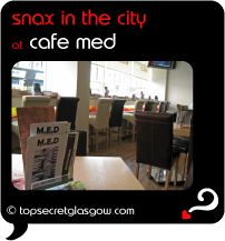 Top Secret Quote Bubble in black, with photo of menus and tables, towards the windows.  Caption: 'snax in the city'