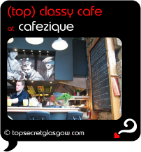 Top Secret Quote Bubble in black, with photo of waiter collecting drinks at bar, photo of Zique behind, blackboard to right. Caption: 'top classy cafe'