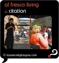 Top Secret Quote Bubble in black, with photo of waiter tending to terrace tables in sunshine. Caption: 'al fresco living'