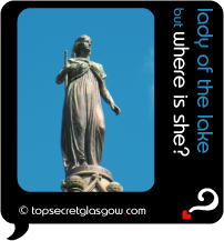 Top Secret Quote Bubble in black, with statue of lady in long gown, bright blue sky.