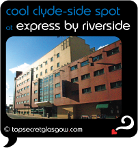 Top Secret Glasgow lozenge showing building shining is sun from across empty street. Caption: cool clyde-side spot
