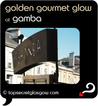 Top Secret Quote Bubble in black, with photo of the Gamba signage against fuzzy backdrop of blond sandstone townhouses bathed in golden light against blue washed sky.  Caption: 'golden gourmet glow'