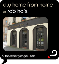 Top Secret Quote Bubble in black, with photo of a sunny exterior corner of Rab's Ha's.  Caption: 'city home from home'