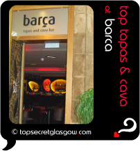 Top Secret Quote Bubble in black, with photo of entranceway of Barca;  glowing interior of chic modern bar with orange and lemon lights. Caption: 'top tapas & cava'
