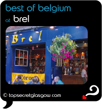 Top Secret Quote Bubble in black, with photo of exterior of Brel; bright blue painted walls with acid yellow signage, bright hanging floral baskets.  Pavement tables and chairs. Caption: 'best of belgium'