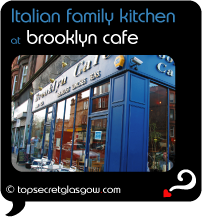 Top Secret Quote Bubble in black, with photo of exterior of Brooklyn Cafe; bright blue painted walls with brass signage, reflections of surrounding red sandstone buildings in windows. Caption: 'Italian family kitchen'