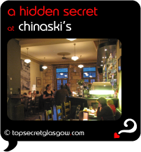 Top Secret Quote Bubble in black, with photo of interior in evening, towards the bar. Caption: 'a hidden secret'