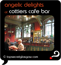 Top Secret Quote Bubble in black, with interior image of Cottier's bar, with 2 women at a table.  Caption in orange: 'angelic delights'