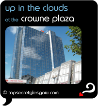 Top Secret Quote Bubble in black, with photo of crowne plaza's mirrored glass tower against a lightly cloudy  blue sky.  Caption: 'up in the clouds'