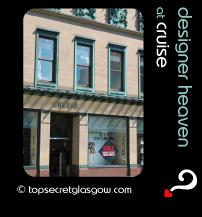 Top Secret Quote Bubble in black, with exterior image of shop front, in sunshine. Caption: 'designer heaven'