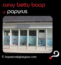 Top Secret Glasgow Quote Bubble showing sunny exterior of shop front. Caption: curvy betty boop