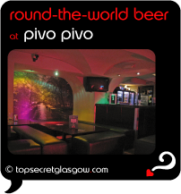 Top Secret Quote Bubble in black, with photo of bar area with funky red and orange lighting. Caption: 'round-the-world beer'