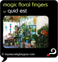 Top Secret Quote Bubble in black, with photo of interior surrounded by plants, flowers and gifts. Caption: 'magic floral fingers'