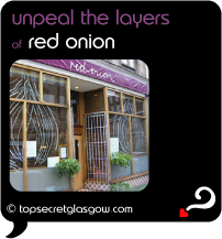 Top Secret Quote Bubble in black, with photo of exterior with topiaries and twin window vinyls of onions.  Caption: 'unpeal the layers'