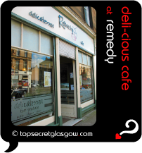 Top Secret Quote Bubble in black, with photo of the shop front, reflecting Mulberry Street.  Caption: 'deli-cious cafe'