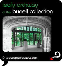 Top Secret Quote Bubble in black, with photo of interior of Burrell Collection; large arched artifact with leafy engravings built into exhibit space with other pedestals in mid distance and bright green leafy exterior beyond through glass wall. Caption: 'leafy archway'