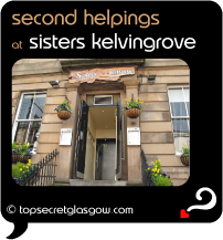 Top Secret Quote Bubble in black, with photo of blond sandstone exterior of Sisters Kelvingrove; looking up steps to entrance doorway from pavement, yellow flowers everywhere in hanging baskets and window boxes.  Caption: 'second helpings'